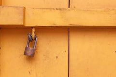 Cadeado oxidado velho que pendura na parede de madeira amarela Imagem de Stock