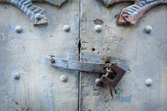Cadeado preto do metal em portas velhas de madeira verdes da garagem com punho Fotografia de Stock