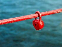 Cadeado vermelho sob a forma do coração na cerca fotografia de stock royalty free