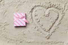 Cadeau à côté de symbole de forme de coeur Photographie stock