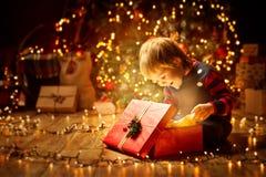 Cadeau actuel ouvert d'enfant de Noël, bébé garçon heureux regardant la boîte photographie stock