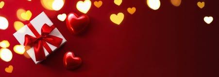 Cadeau avec des coeurs sur le fond rouge Photographie stock