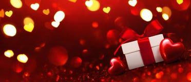 Cadeau avec des coeurs sur le fond rouge Photographie stock libre de droits
