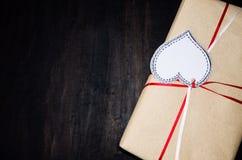 Cadeau avec le coeur de label dessiné sur le fond en bois noir Photos libres de droits