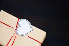 Cadeau avec le coeur de label dessiné sur le fond en bois noir Images stock