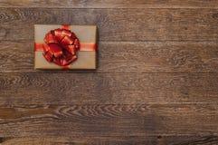 Cadeau avec un ruban rouge et arc sur un fond en bois foncé Image stock
