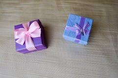 Cadeau, belles, de fête boîtes bleues et pourpres avec un arc et un papillon roses image stock