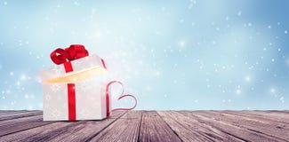 Cadeau blanc ouvert brillant avec le coeur rouge sur la table en bois illustration libre de droits