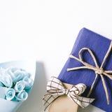 Cadeau bleu et bouquet bleu de fleur sur le fond blanc Photographie stock