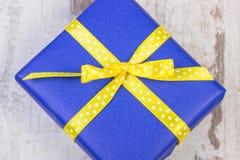 Cadeau bleu pour Noël ou toute autre célébration sur la planche en bois Photo stock