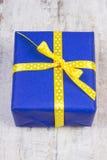 Cadeau bleu pour Noël ou toute autre célébration sur la planche en bois Images stock