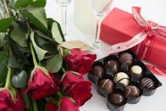 Cadeau, boîte à chocolat, roses et bouteille de champagne sur le fond blanc Photo stock