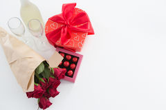 Cadeau, boîte à chocolat, roses et bouteille de champagne sur le fond blanc Images stock