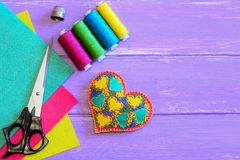 Cadeau brodé de coeur pour le jour de valentines L'ornement de coeur de feutre, fil, ciseaux, dé, feutre couvre sur un fond en bo Photographie stock libre de droits