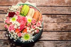 Cadeau d'amour avec des fleurs et des macarons Photographie stock libre de droits