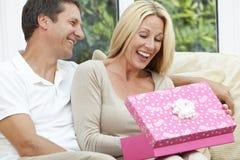 Cadeau d'anniversaire heureux d'ouverture de couples d'homme et de femme Images stock