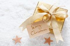 Cadeau d'or avec l'étiquette de Joyeux Noël image libre de droits