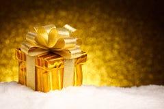 Cadeau d'or de Noël dans la neige Photographie stock