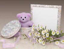 Cadeau d'ours de nounours avec une trame et des fleurs de photo Image stock
