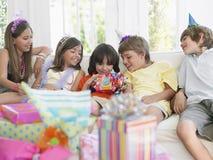Cadeau d'ouverture de garçon avec des invités à la partie Photos stock