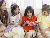 Cadeau d'ouverture de garçon avec des invités à la partie Image libre de droits