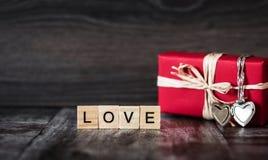 Cadeau dans la boîte rouge, un pendant sous forme de coeur sur un argent c Photographie stock