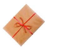 Cadeau dans le papier d'emballage et le ruban rouge bandé d'isolement sur le fond blanc avec l'espace pour le texte Images libres de droits