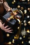 Cadeau dans les mains d'une fille sur le fond d'un sapin Photo libre de droits