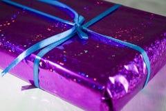 Cadeau dans un emballage violet et brillant avec un ruban bleu avec un arc image stock
