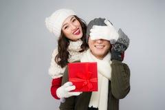 Cadeau de couples Jeune femme donnant le cadeau à l'ami sur le backg blanc Images libres de droits