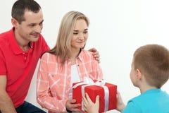 Cadeau de dissimulation de fils pour étonner la maman le jour du ` s de mère La femme, équipent Photographie stock libre de droits