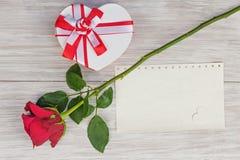 Cadeau de jour du ` s de Valentine, rose et de papier sur le fond en bois. Images stock