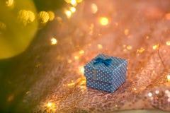 Cadeau de NBlue sur un fond de corail contre un arbre brouillé de nouvelle année décoré de l'or et des boules bleues photos libres de droits