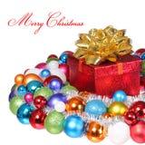 Cadeau de Noël avec l'arc d'or et les boules colorées d'isolement sur le petit morceau Photographie stock libre de droits