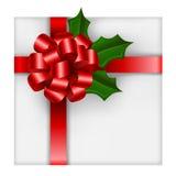 Cadeau de Noël avec l'arc et le houx rouges Photographie stock libre de droits