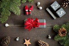 Cadeau de Noël avec le ruban, le calendrier de Noël, les branches de pin, le cône et les décorations rouges de Noël Photo libre de droits