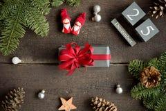 Cadeau de Noël avec le ruban, le calendrier de Noël, les branches de pin, le cône et les décorations rouges de Noël Images libres de droits