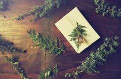 Cadeau de Noël avec les brindilles à feuilles persistantes naturelles sur le fond en bois Configuration plate Copiez l'espace images libres de droits