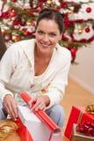 Cadeau de Noël d'emballage de jeune femme Photographie stock libre de droits
