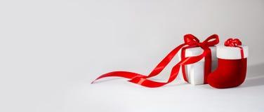 Cadeau de Noël dans le boîtier blanc avec le ruban et le Toy Sock rouges sur le fond clair Bannière de composition en nouvelle an image libre de droits