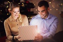 Cadeau de Noël heureux d'ouverture de couples Photo stock