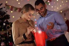 Cadeau de Noël heureux d'ouverture de couples Photographie stock libre de droits