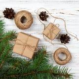Cadeau de Noël ou boîte actuelle enveloppée en papier d'emballage avec la décoration sur le fond en bois rustique Photos stock