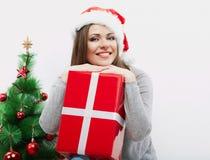Cadeau de Noël de prise de verticale de femme d'isolement par chapeau de Santa de Noël Photographie stock