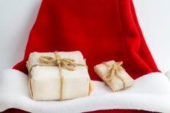 Cadeau de Noël sur le chapeau de Santa sur le fond blanc Photographie stock libre de droits