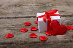 Cadeau de vacances et coeurs rouges sur le fond en bois Photographie stock