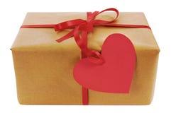 Cadeau de Valentine, colis de papier brun, étiquette rouge de cadeau de forme de coeur photographie stock