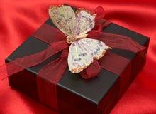 Cadeau de Valentines sur la soie rouge Photographie stock
