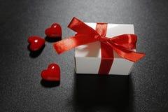 Cadeau du ` s de Valentine avec le ruban rouge et les coeurs en verre Photographie stock libre de droits