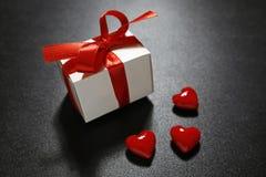 Cadeau du ` s de Valentine avec le ruban rouge et les coeurs en verre Image stock